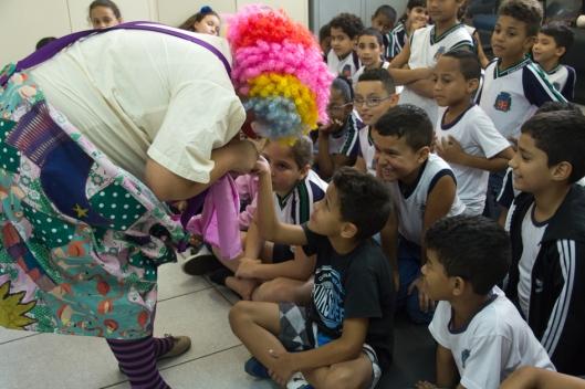 Gigi Fernandes brinca de quiromante com as crianças de Cubatão. Foto: Bruna Quevedo (Just Design).